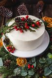 Homemade white cream naked cake decorated with white cream, cones and red berries. royalty free stock photo