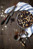 homemade whole dark chocolate and almonds cake on wooden table Stock Photo
