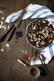 Homemade whole dark chocolate and almonds cake on wooden table Royalty Free Stock Photography