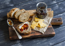 Homemade whole grain bread, cheese and figs jam.  Delicious breakfast or snack. On a wooden rustic board Royalty Free Stock Photo