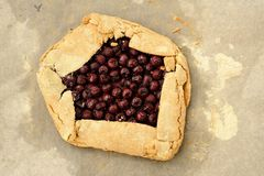 Homemade wholegrain galette with fresh cherries on baking paper. Overhead view Stock Photography