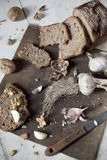Homemade wholemeal sliced bread with walnuts and whole and clove of garlic Royalty Free Stock Photos