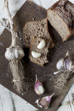 Homemade wholemeal sliced bread with whole and clove of garlic Stock Image