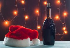 Homemade wine on Christmas table on a background of burning lights,. Santa`s hat on wooden table Royalty Free Stock Image
