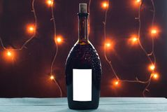 Homemade wine on Christmas table on a background of burning lights,. Wooden table, a template for labels Royalty Free Stock Photo