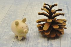 Wooden figure of piglet and big beautiful pine cone on light background decorated with snowflakes. royalty free stock photos