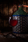 Homemade wine from young grapes Izabella . On the table is a large wicker bottle of homemade wine from young grapes Izabella royalty free stock image