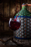 Homemade wine from young grapes Izabella. On the table is a large wicker bottle of homemade wine from young grapes Izabella . In the glass of wine and a splash royalty free stock images