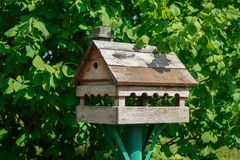 Wooden bird feeder on the background of green foliage. Homemade wooden birdhouse on a background of green foliage in summer Royalty Free Stock Photos