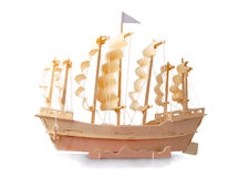Homemade wooden ship with paper sails and flag. Homemade wooden ship with paper sails and a flag on a white background Royalty Free Stock Photos