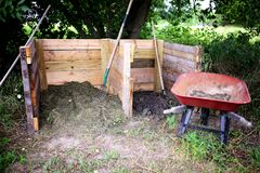 Homemade Wooden 2 Stage Compost Bin with Whell Barrow in the Gar Stock Images