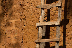 Homemade wooden staircase near the clay wall Stock Photos