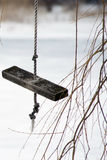 Homemade Wooden Swing. On rope close-up near tree branches over frozen lake in the wintertime Royalty Free Stock Photos