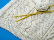 Homemade  woolen sweater. Knitwear in Aran cables of an Irish sweater with yellow knitting-needles and a ball of wool Royalty Free Stock Image