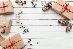 Homemade wrapped rustic brown paper packages with various natural things on white wooden surface.  Stock Image