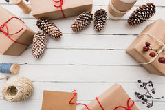 Homemade wrapped rustic brown paper packages with various natural things on white wooden surface.  Stock Photo