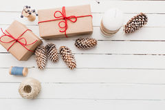 Homemade wrapped rustic brown paper packages with various natural things on white wooden surface.  Stock Photography