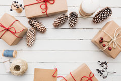 Homemade wrapped rustic brown paper packages with various natural things on white wooden surface.  Royalty Free Stock Image