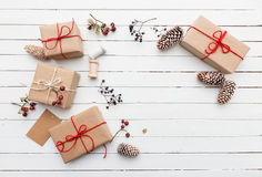 Homemade wrapped rustic brown paper packages with various natural things on white wooden surface Stock Photo