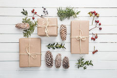 Homemade wrapped rustic brown paper packages with various natural things on white wooden surface Royalty Free Stock Photo