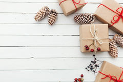 Homemade wrapped rustic brown paper packages with various natural things on white wooden surface.  Stock Images