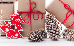 Homemade wrapped rustic brown paper packages with various natural things on white wooden surface.  Royalty Free Stock Photos