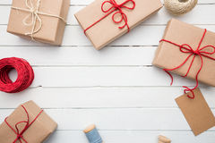 Homemade wrapped rustic brown paper packages on white wooden surface.  Royalty Free Stock Photos