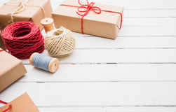 Homemade wrapped rustic brown paper packages on white wooden surface.  Stock Photo