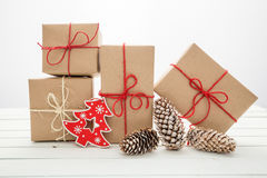 Homemade wrapped rustic brown paper packages on white wooden surface.  Royalty Free Stock Photography