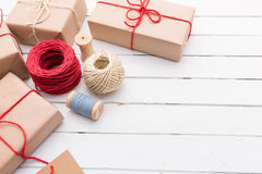 Homemade wrapped rustic brown paper packages on white wooden surface.  Stock Photos