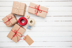 Homemade wrapped rustic brown paper packages on white wooden surface.  Royalty Free Stock Photo