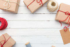 Homemade wrapped rustic brown paper packages on white wooden surface Royalty Free Stock Photos