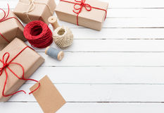 Homemade wrapped rustic brown paper packages on white wooden surface Royalty Free Stock Photo
