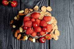 Homemade yoghurt with flakes, nuts and berries of raspberries and cherries stock image