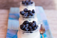 Homemade yogurt with berries in a glass jar. Homemade yogurt with blueberries in a glass jar Royalty Free Stock Photo