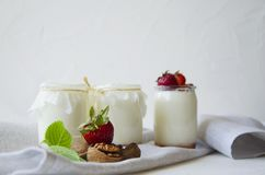 Homemade yogurt with fresh strawberries. Ingredients for a healthy breakfast are halves of strawberries, walnuts and yogurt with royalty free stock photography