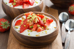 Homemade yogurt with fresh strawberries and pistachios in bowl Stock Images