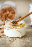 Homemade yogurt with honey and nuts. In a glass jar Stock Photos