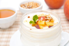 Homemade yogurt with honey, peaches and nuts, close-up Stock Photography