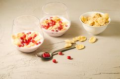 Homemade yogurt with pomegranate and flakes in glass/homemade yogurt with pomegranate and flakes in glass and flakes in a bowl on. A white stone table breakfast stock photos