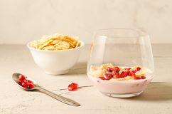 Homemade yogurt with pomegranate in glass and a bowl of flakes/homemade yogurt with pomegranate in glass and a bowl of flakes on a. White stone table, selective royalty free stock photo