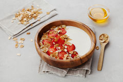 Homemade yogurt in wooden bowl with strawberry and granola or muesli on light table, healthy breakfast Stock Photos