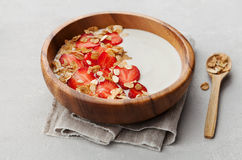 Homemade yogurt in wooden bowl with strawberry and granola or muesli on light table, healthy breakfast royalty free stock image