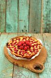 Homemade yummy cake with fresh raspberries on wooden board. Vertical Royalty Free Stock Photo