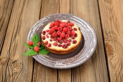 Homemade yummy cake with fresh wild raspberries and leaves in br. Own plate on old wooden table copyspace horizontal Royalty Free Stock Photography