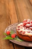 Homemade yummy cake with fresh wild raspberries and leaves decor. Ated with icing sugar in brown plate on old rustic table copyspace vertical Stock Images