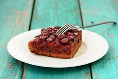 Homemade yummy chocolate cake with cherries with fork in white p. Late on turquoise table copyspace Stock Images