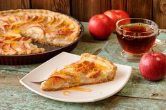 Homemade yummy open apple pie, black tea and whole red apples on Stock Image