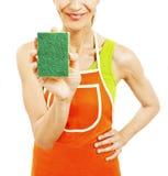 Homemaker в рисберме держа шайбу губки стоковые изображения