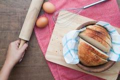 Homemaker держа вращающую ось с отрезанным домодельным хлебом на древесине стоковые изображения rf
